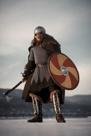 Medieval Scandinavian warrior Viking in full outfit on shore of winter sea Banco de Imagens