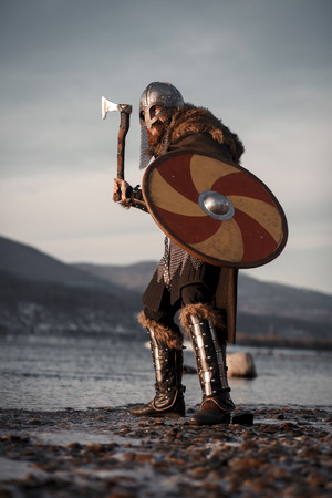 Medieval Scandinavian warrior Viking in full outfit on shore of winter sea 版權商用圖片 - 115615156