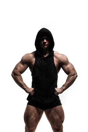 Handsome power athletic man pumping up muscles in anonymous hoodie isolated over white. Strong bodybuilder with perfect shape body and six pack, abs, shoulders, biceps, triceps and wide back. Banco de Imagens