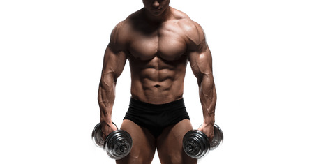 Handsome power athletic man in training muscles with dumbbells isolated over white. Strong bodybuilder with perfect shape body and six pack, abs, shoulders, biceps, triceps and chest. Close up Banco de Imagens