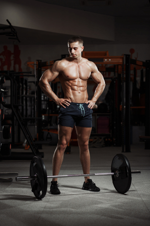 Power very athletic guy standing with barbell. Workout in the gym Banco de Imagens
