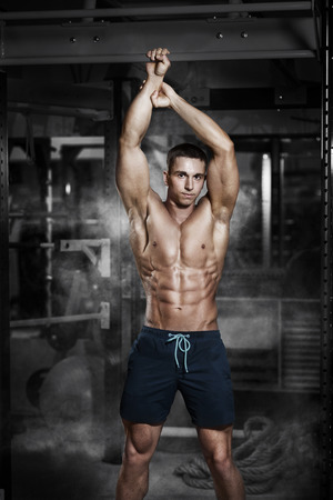Athlete muscular fitness male model stand with horizontal bar in a gym