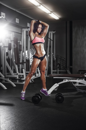 Sexy athlete fitness girl posing with a dumbbell in the gym 版權商用圖片