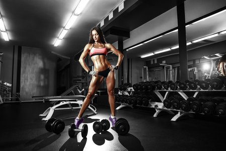 Sexy athlete fitness girl with a dumbbell in the gym
