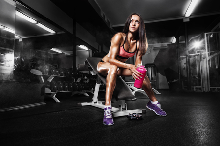 fitness girl with shaker posing on bench in the gym Banco de Imagens