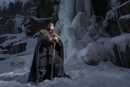Mittelalterliche Ritter mit Schwert in Rüstung gehen in Winter Rock Landscapes