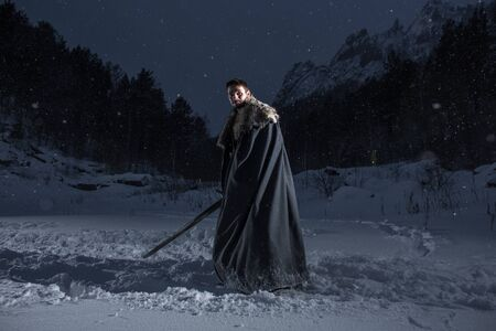 Medieval knight with sword in armor in Winter Rock Landscapes Stock fotó