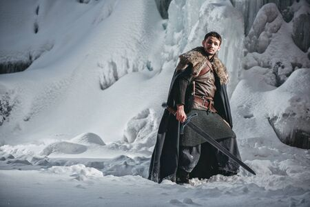 Medieval knight with sword in Armour  going in Winter Rock Landscapes 免版税图像
