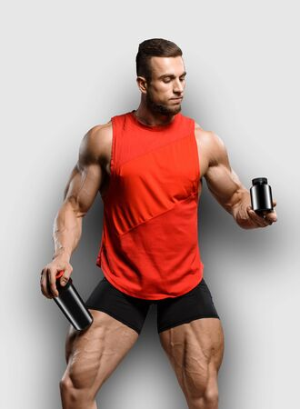 Muscular bodybuilder guy shows his muscles and holds sport nutrition supplement in brutal powerful hand isolated over gray background. Workout bodybuilding concept. 免版税图像