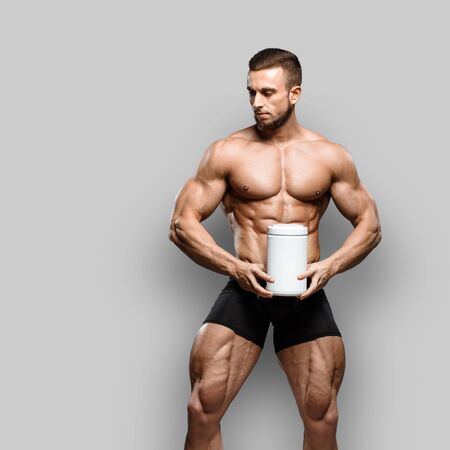 Muscular bodybuilder guy shows his perfect abs sixpack and holds sport nutrition supplement in brutal powerful hand isolated over gray background. Workout bodybuilding concept. background.
