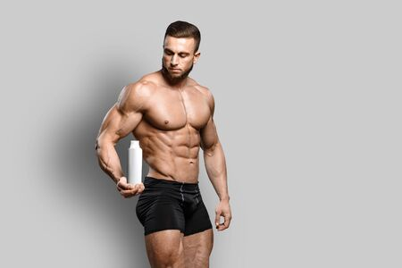 Muscular bodybuilder guy shows his perfect abs sixpack and holds sport nutrition supplement in brutal powerful hand isolated over gray background. Workout bodybuilding concept.