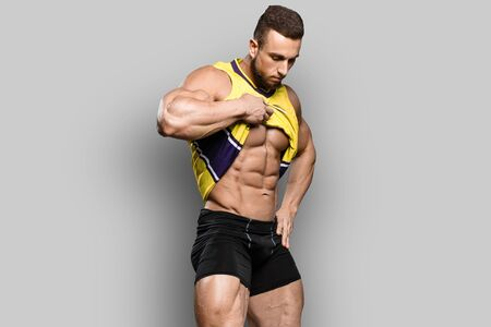 Muscular bodybuilder guy shows his perfect abs sixpack and holds t-shirt in brutal powerful hand  isolated over gray background. Workout bodybuilding concept.