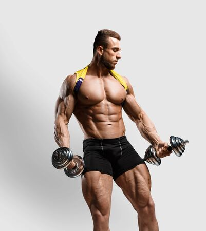 Muscular bodybuilder fitness man doing exercises with dumbbells isolated over gray background. Workout bodybuilding concept.