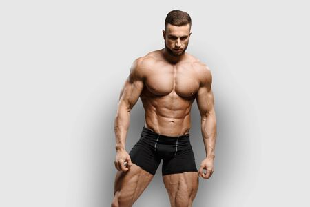 Muscular bodybuilder fitness man with perfect body  shows muscles isolated over gray background. Workout bodybuilding concept.