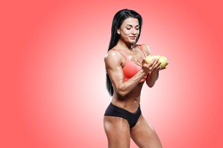 attractive sports woman holding fresh fruit in hands on red. muscled  body fitness girl on diet nutrition 免版税图像