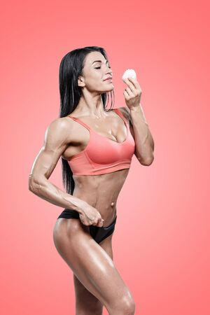 attractive sports woman holding sugar cake in hands on red. muscled  body fitness girl on diet nutrition