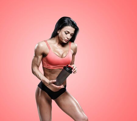 Sporty girl drinking water after workout. Photo of fitness girl on red background. Healthy lifestyle 免版税图像