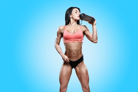 Sporty girl drinking water or ptotein supplements after workout. Photo of fitness girl on blue background. Healthy lifestyle
