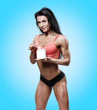 attractive sports woman drinking protein supplement from sport bottle on grey. muscled  body fitness girl with sport nutrition