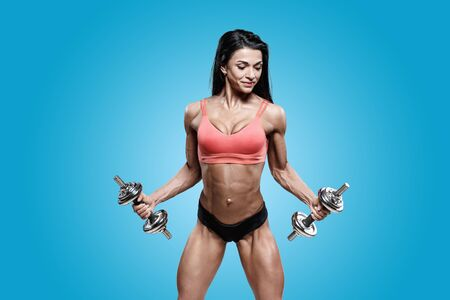 Sporty woman in black and red sportswear holding dumbbells. Photo of muscular woman in training pumping up muscles of hands and legs on blue background. Strength and motivation sport concept photo