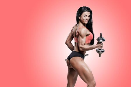 Sporty woman in black and red sportswear holding dumbbells. Photo of muscular woman in training pumping up muscles of hands and legs on red background. Strength and motivation sport concept photo