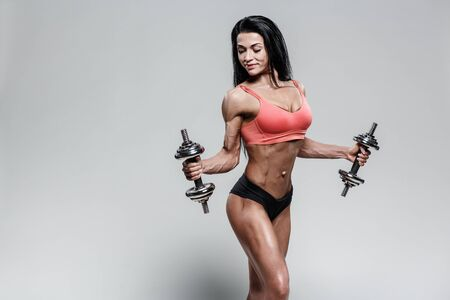 Sporty woman in black and red sportswear holding dumbbells. Photo of muscular woman in training pumping up muscles of hands and legs on grey background. Strength and motivation sport concept photo