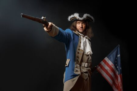 Man in form of officer of United States Revolutionary War with a flag and gun. July 4th, Independence Day USA Concept. Studio photo on black background