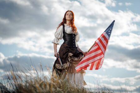 Mädchen im historischen Kleid des 18. Jahrhunderts mit Flagge der Vereinigten Staaten. 4. Juli ist US-Unabhängigkeitstag. Frau des Patrioten-Freiheitskämpfers im Freien auf bewölktem Himmel des Hintergrundes Standard-Bild