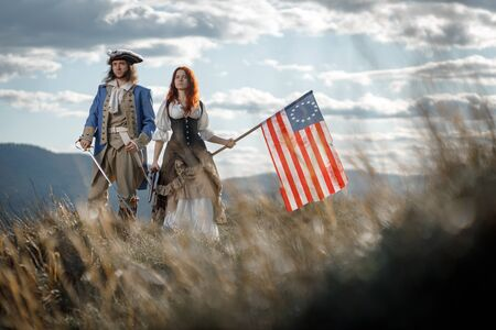 Man in form of officer of War of Independence and girl in historical dress of 18th century. July 4 is US Independence Day. Couple of patriots freedom fighters in outdoor on background cloudy sky