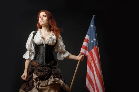 Girl in historic dress from United States Revolutionary War with flag. July 4th, Independence Day USA Concept Photo Composition 免版税图像