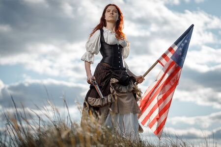 Girl in historical dress of 18th century with flag of United States. July 4 is US Independence Day. Woman of patriot freedom fighter in outdoor on background cloudy sky 免版税图像