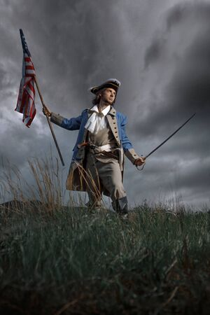 Man in United States War of Independence soldier costume with flag posing in forest. 4 july independence day of USA concept photo composition 免版税图像 - 147460409