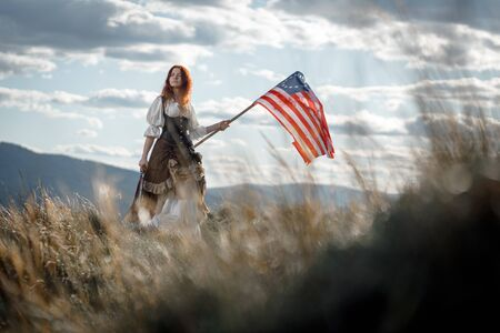 Girl in historical dress of 18th century with flag of United States. July 4 is US Independence Day. Woman of patriot freedom fighter in outdoor on background cloudy sky Banco de Imagens