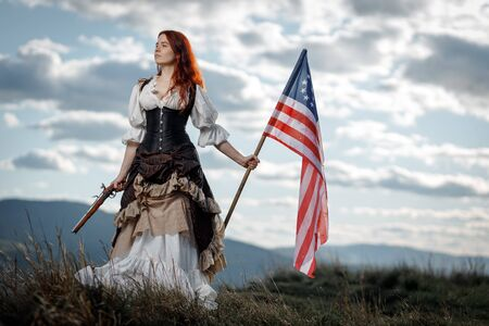 Girl in historical dress of 18th century with flag of United States. July 4 is US Independence Day. Woman of patriot freedom fighter in outdoor on background cloudy sky Foto de archivo