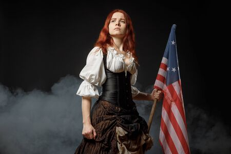 Girl in historic dress from United States Revolutionary War with flag. July 4th, Independence Day USA Concept Photo Composition Banco de Imagens