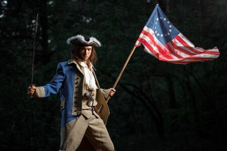 Soldier patriot rebel during war of independence of  United States with flag preparing to attack with sword Banco de Imagens