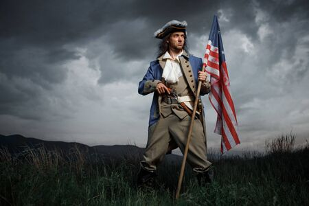Man in United States War of Independence soldier costume with flag posing in forest. 4 july independence day of USA concept photo composition