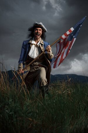 American revolution war soldier with flag of colonies over dramatic landscape. 4 july independence day of USA concept photo composition: soldier and flag.