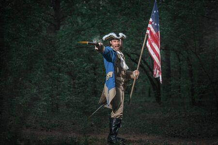 Epic Portrait of man dressed as soldier of american revolution war of United States aims from pistol with flag. 4 july independence day of USA concept photo composition: soldier and flag. 免版税图像 - 147460485