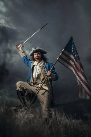 American revolution war soldier with flag of colonies and saber over dramatic landscape. 4 july independence day of USA concept photo composition: soldier and flag. 免版税图像 - 147460491