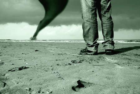 man watching the tornado on the beach photo