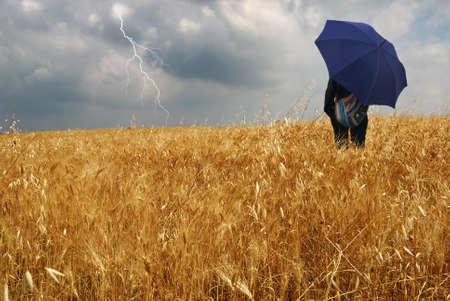 man into corn field with umbrella photo