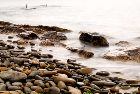 isolated brown rocks near the shore photo