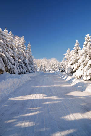 snowy mountain road with blue sky photo