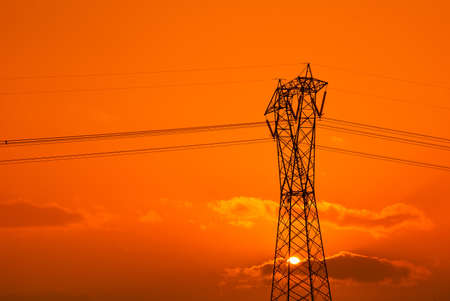 isolated high voltage pylon on orange sky photo