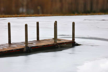 isolated wooden pier over icy water photo
