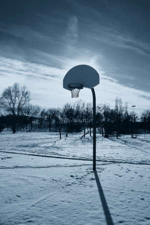 basketball court at sunset covered by snow photo