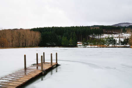 wooden pier in winter with frozen water photo
