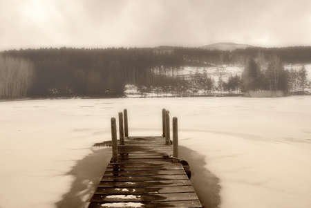 frozen lake: old wooden pier in the woodland