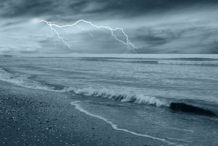 dramatic sea with dark clouds and lightning photo